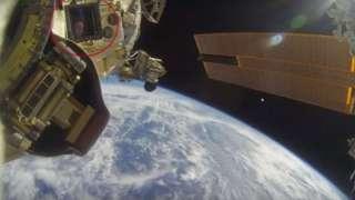 В иллюминаторе МКС в открытом космосе отразился человек в синей шапке